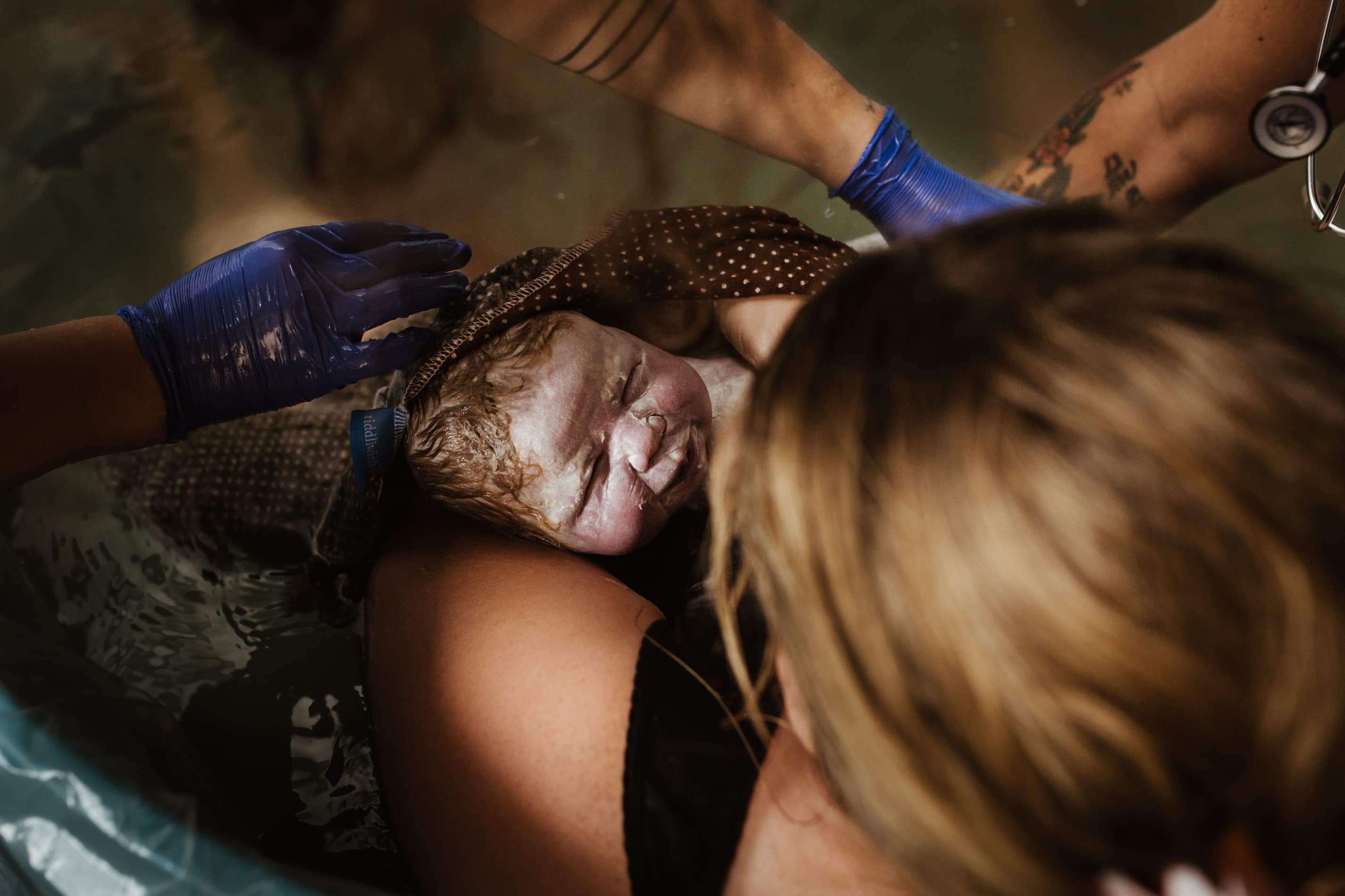 overhead shot of vernix covered baby just born held in Moms arms