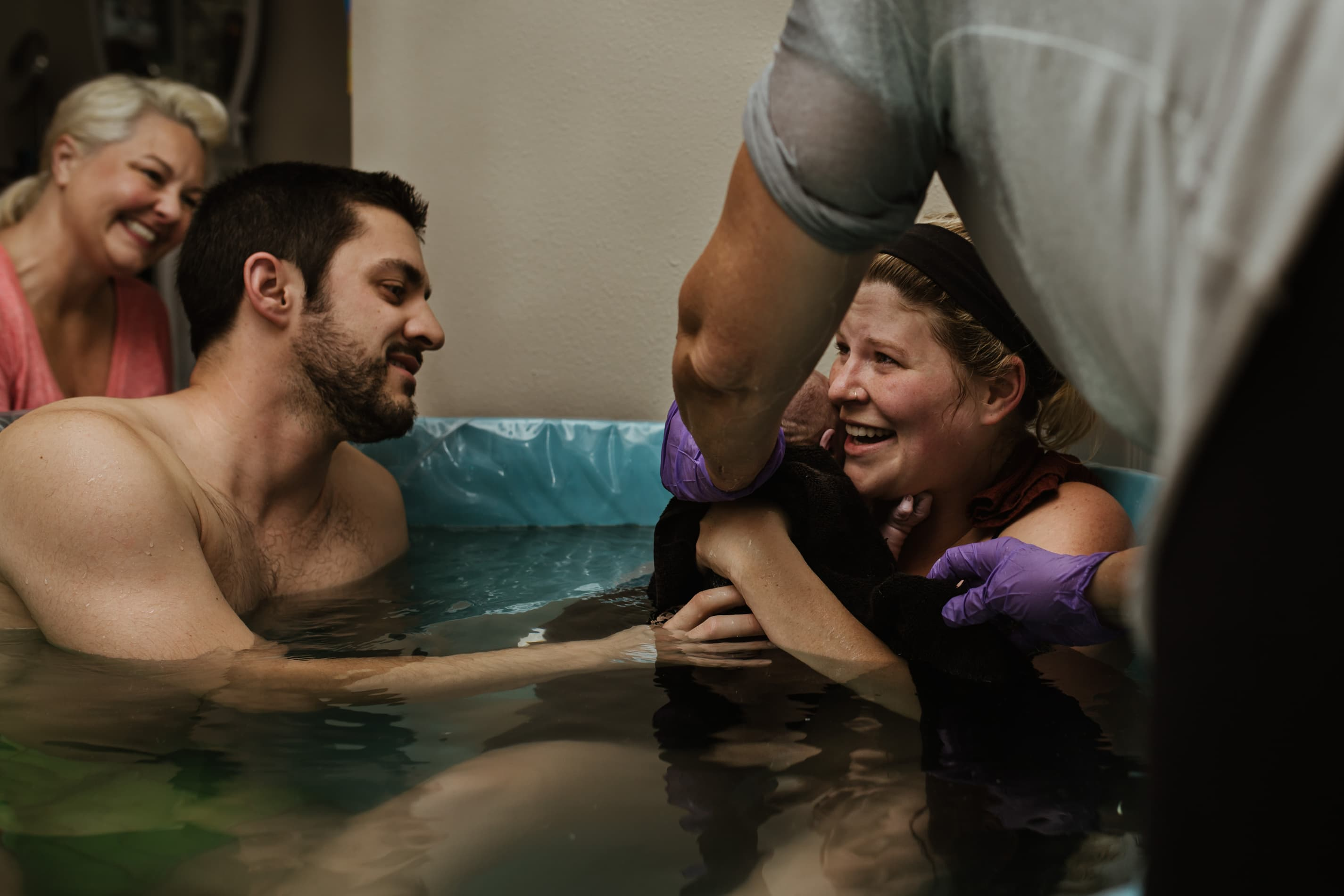 midwife assisted home birth mom receiving baby with excitement dad also in the tub reaching out to touch new baby