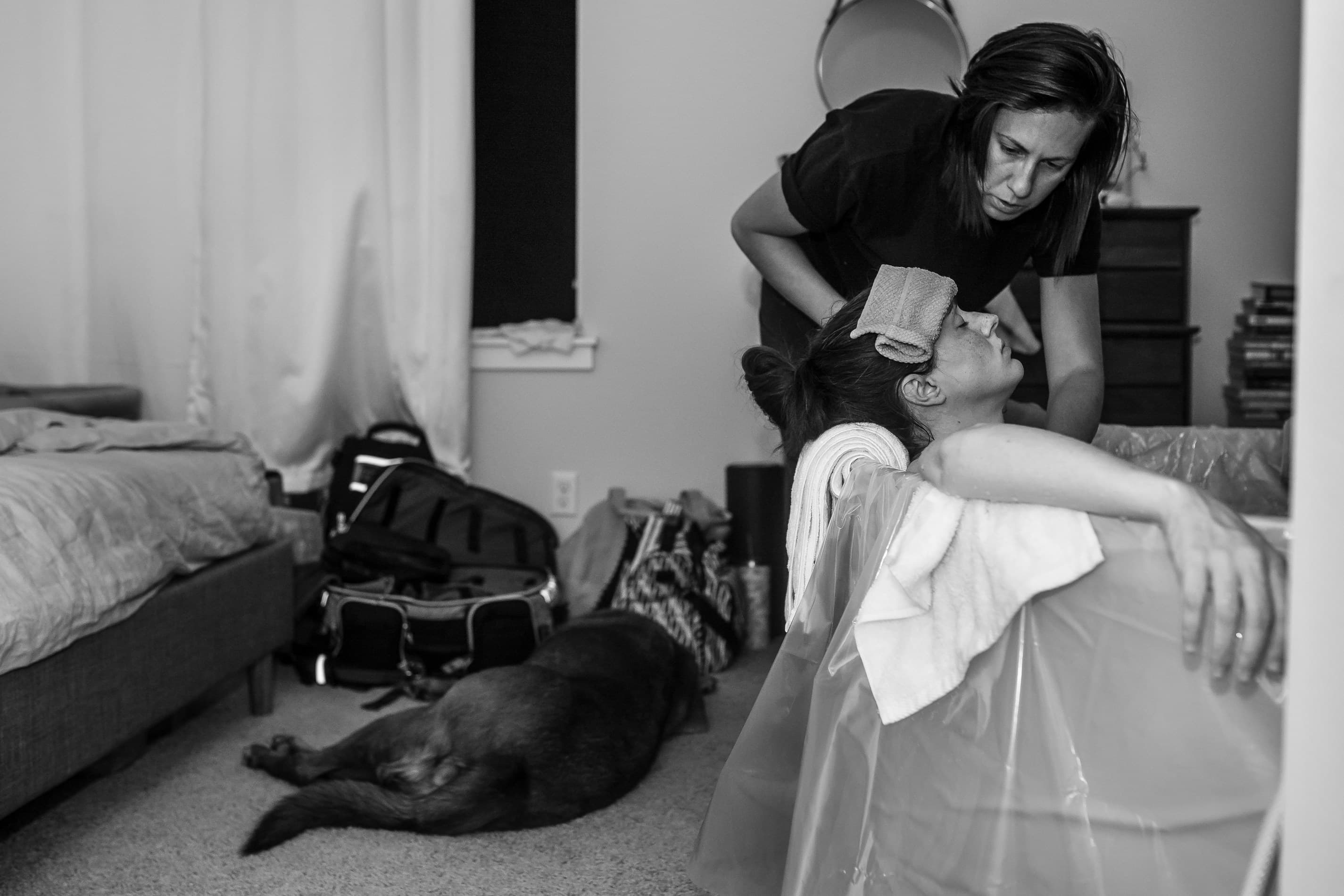 Wife attentively cares for her wife while laboring at home, the family dog laying on the floor behind them