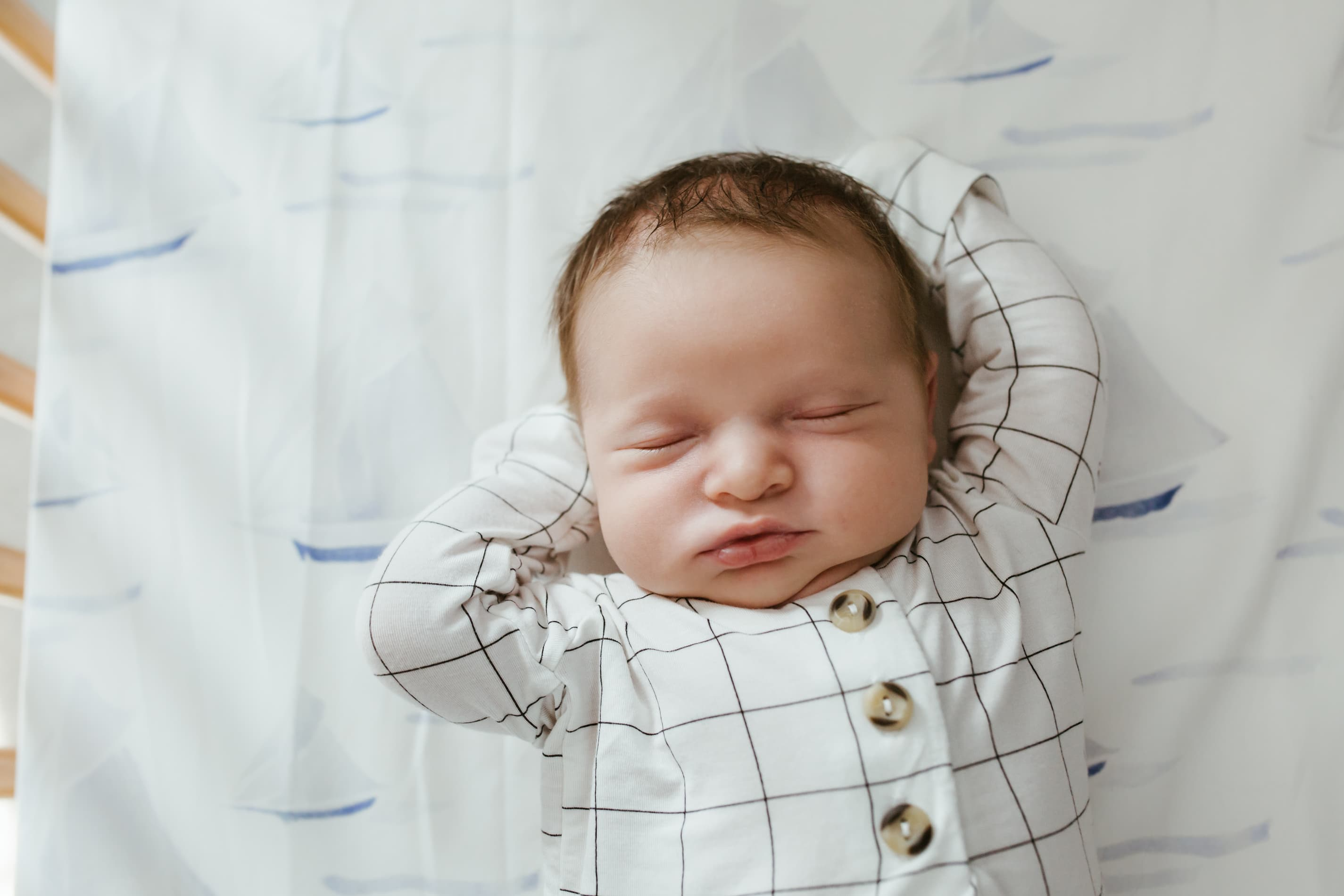 overhead image of a sleepy newborn stretching while laying in his sailor themed crib