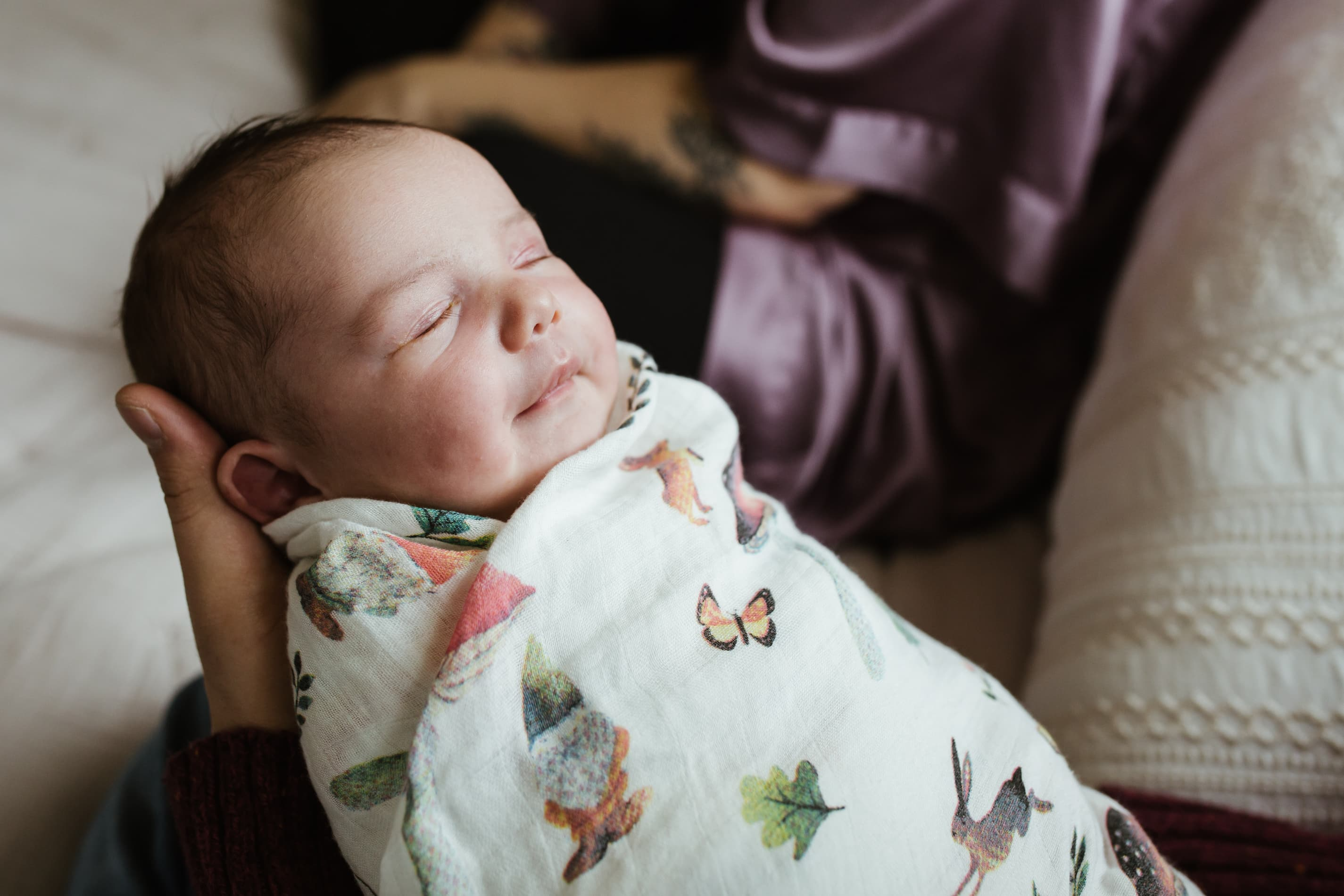 family documentary session newborn baby swaddles in brightly colored muslin blanket being held by her dad