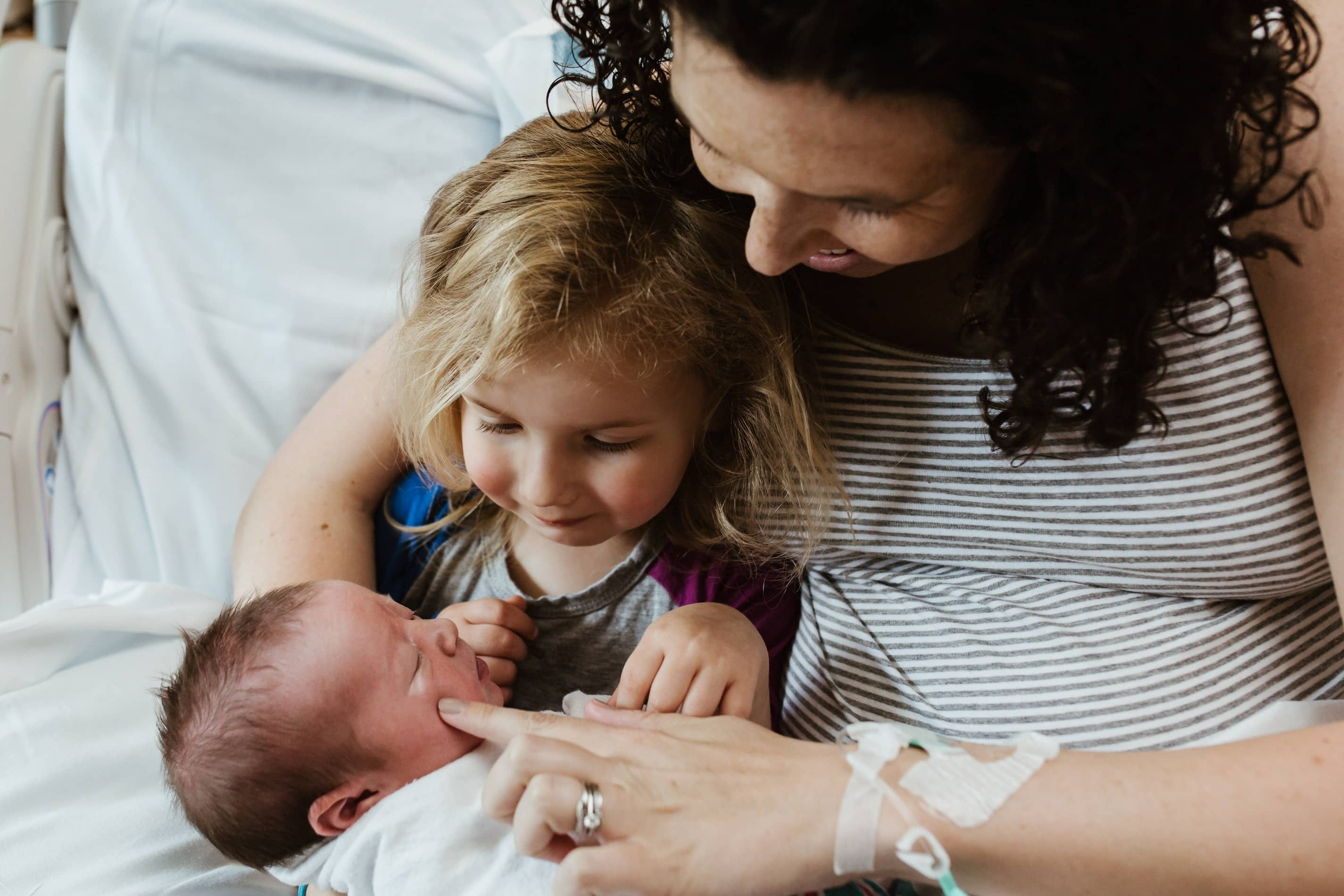hospital fresh 48 session mom toddler and new baby snuggle in bed together