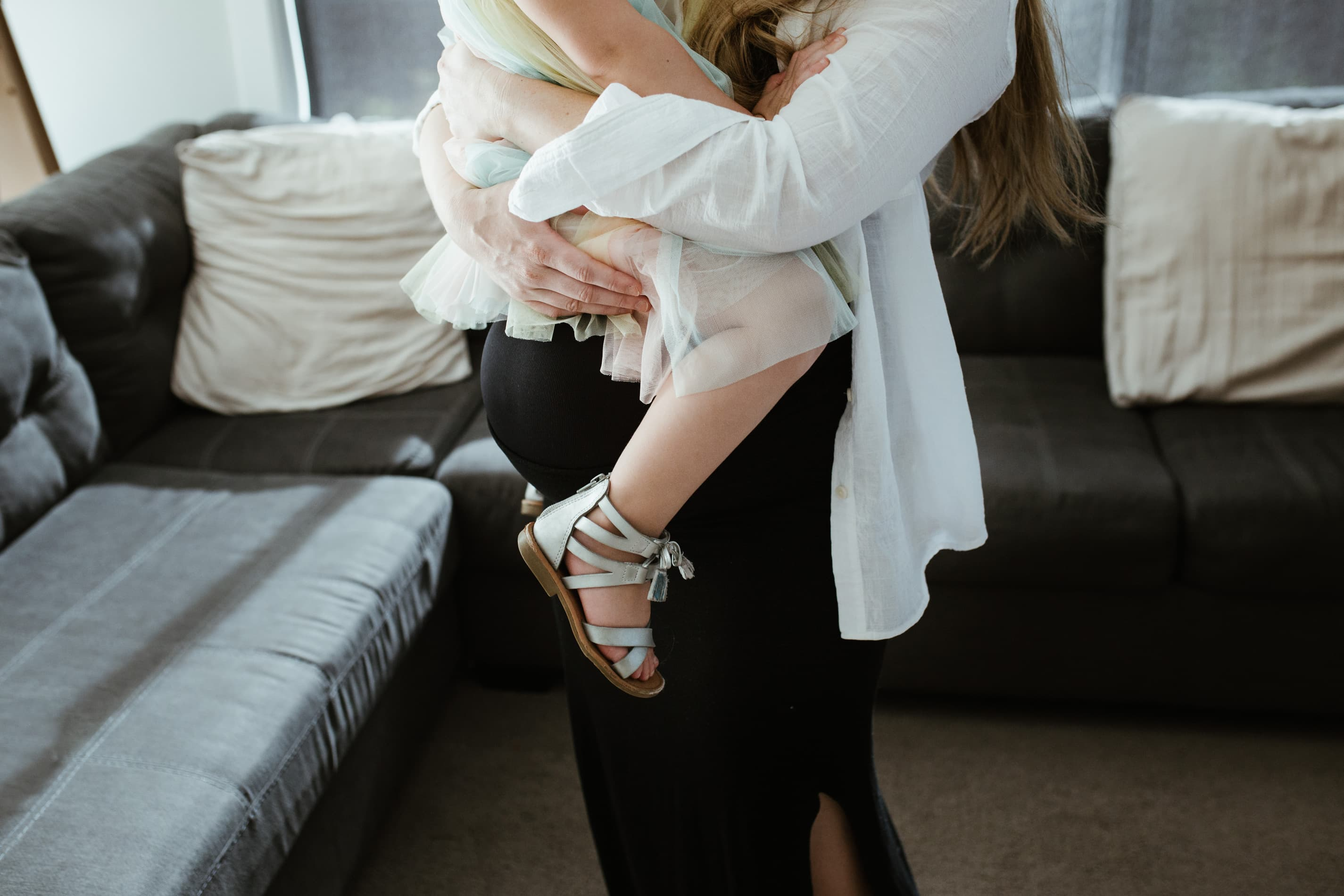 pregnant mom holds toddler over her bump during in home maternity session