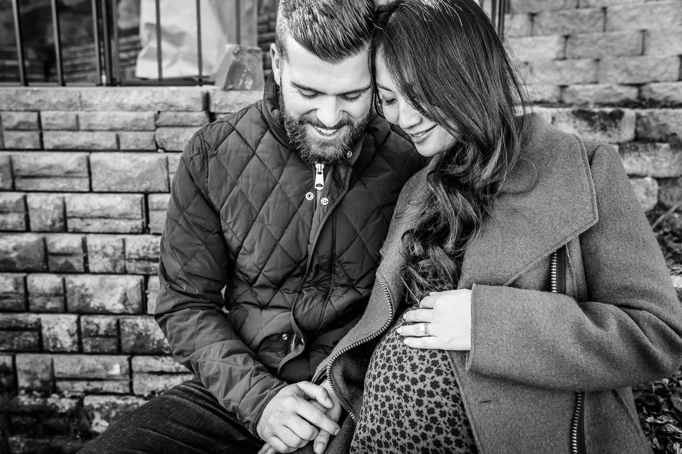 mixed race couple snuggling outside while sitting dad holding her hand while mom holds her pregnant belly